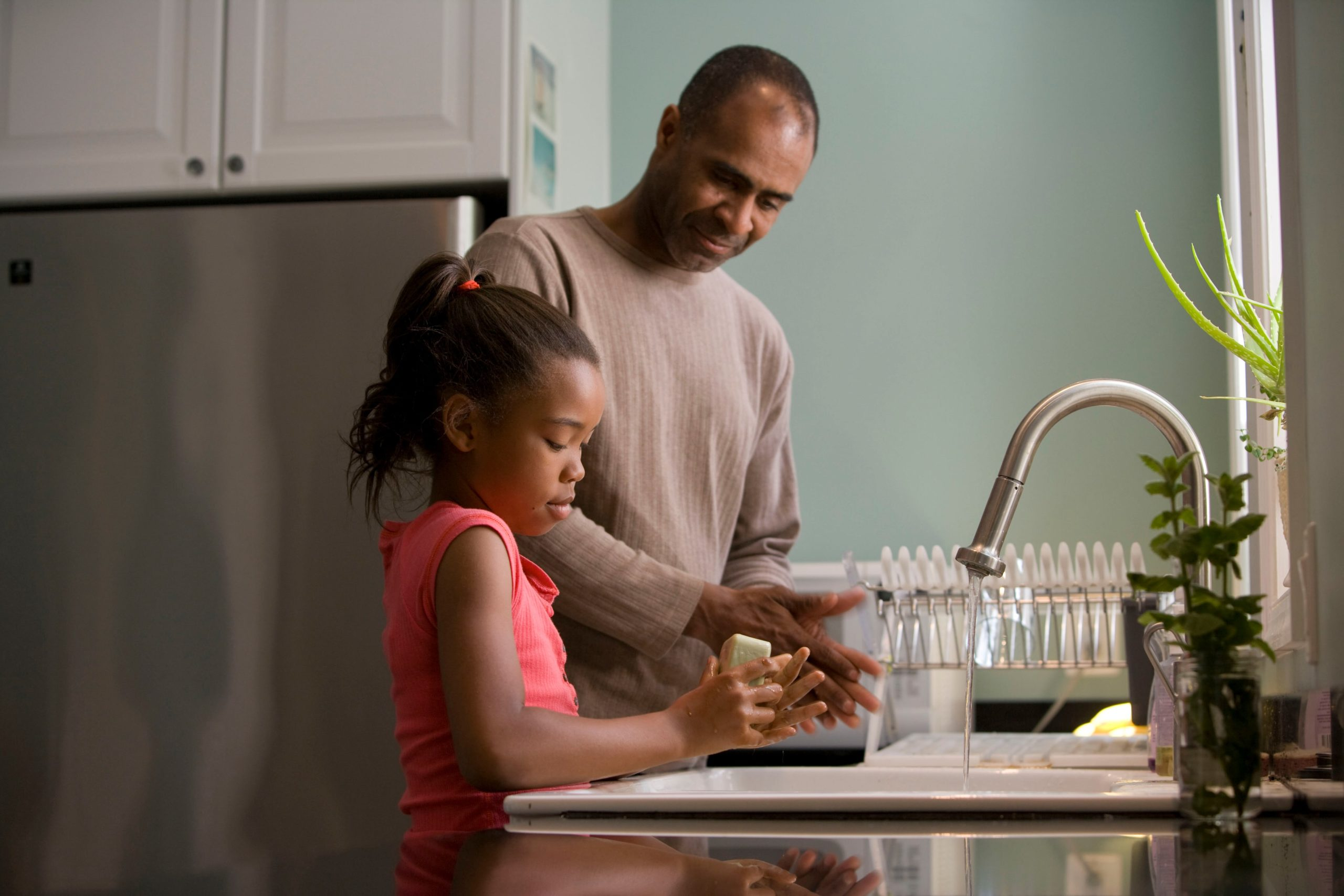 father and daughter washing hands
